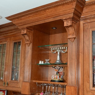 Example of a classic kitchen design in New York with medium tone wood cabinets and an island