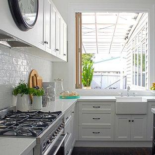 メルボルンの中サイズのヴィクトリアン調のおしゃれなキッチン (エプロンフロントシンク、落し込みパネル扉のキャビネット、白いキャビネット、クオーツストーンカウンター、白いキッチンパネル、磁器タイルのキッチンパネル、シルバーの調理設備の、濃色無垢フローリング) の写真