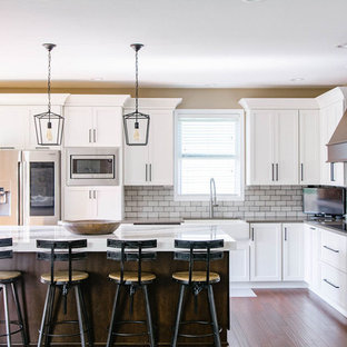 Transitional kitchen ideas - Kitchen - transitional l-shaped medium tone wood floor kitchen idea in Omaha with a farmhouse sink, shaker cabinets, white cabinets, gray backsplash, subway tile backsplash, stainless steel appliances, an island and gray countertops