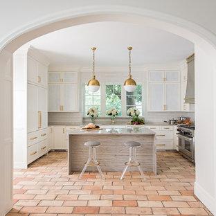 На фото: большая п-образная, отдельная кухня в стиле современная классика с врезной раковиной, фасадами в стиле шейкер, белыми фасадами, столешницей из кварцита, белым фартуком, фартуком из керамической плитки, техникой под мебельный фасад, полом из терракотовой плитки и островом с