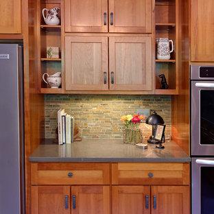 シアトルの巨大なおしゃれなキッチン (一体型シンク、シェーカースタイル扉のキャビネット、中間色木目調キャビネット、人工大理石カウンター、緑のキッチンパネル、石タイルのキッチンパネル、シルバーの調理設備、磁器タイルの床) の写真