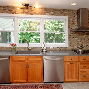 シアトルの巨大なラスティックスタイルのおしゃれなキッチン (一体型シンク、シェーカースタイル扉のキャビネット、中間色木目調キャビネット、人工大理石カウンター、緑のキッチンパネル、石タイルのキッチンパネル、シルバーの調理設備の、磁器タイルの床) の写真