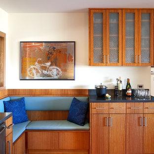 Inspiration pour une cuisine minimaliste avec un placard à porte vitrée, des portes de placard en bois brun et un électroménager en acier inoxydable.