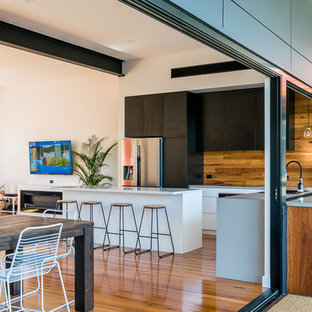 Photo of a mid-sized contemporary l-shaped open plan kitchen in Sydney with quartz benchtops, black appliances, light hardwood floors, with island, white benchtop, flat-panel cabinets, black cabinets, brown splashback, timber splashback and brown floor.
