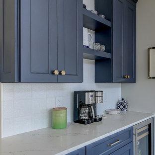 ダラスの広いトランジショナルスタイルのおしゃれなキッチン (エプロンフロントシンク、落し込みパネル扉のキャビネット、青いキャビネット、珪岩カウンター、白いキッチンパネル、セラミックタイルのキッチンパネル、シルバーの調理設備、淡色無垢フローリング、茶色い床、白いキッチンカウンター) の写真