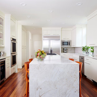 Contemporary kitchen remodeling - Example of a trendy u-shaped medium tone wood floor and brown floor kitchen design in Minneapolis with flat-panel cabinets, white cabinets, stainless steel appliances, an island, white countertops, an undermount sink and white backsplash