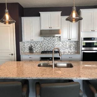 インディアナポリスの小さいシャビーシック調のおしゃれなキッチン (落し込みパネル扉のキャビネット、白いキャビネット、御影石カウンター、マルチカラーのキッチンパネル、モザイクタイルのキッチンパネル、シルバーの調理設備の、クッションフロア、茶色い床、白いキッチンカウンター) の写真