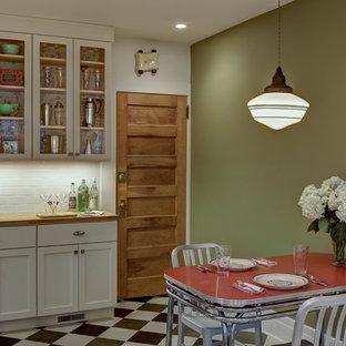ニューヨークの中くらいのトランジショナルスタイルのおしゃれなキッチン (アンダーカウンターシンク、シェーカースタイル扉のキャビネット、白いキャビネット、木材カウンター、白いキッチンパネル、セラミックタイルのキッチンパネル、シルバーの調理設備、リノリウムの床、アイランドなし) の写真