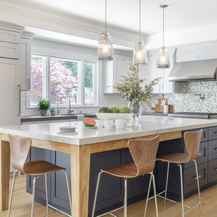 Large transitional l-shaped open plan kitchen in San Francisco with shaker cabinets, white cabinets, grey splashback, panelled appliances, with island, a single-bowl sink, light hardwood floors, marble benchtops, marble splashback, beige floor and white benchtop.
