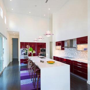 Inspiration pour une cuisine parallèle design avec un placard à porte plane, des portes de placard rouges et une crédence en mosaïque.