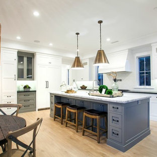 This is an example of an eclectic open plan kitchen in Orange County with grey cabinets, marble benchtops, white splashback, glass tile splashback, stainless steel appliances, light hardwood floors and with island.