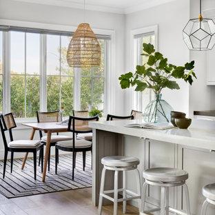 オレンジカウンティの広いトランジショナルスタイルのおしゃれなキッチン (淡色無垢フローリング、茶色い床、三角天井、エプロンフロントシンク、シェーカースタイル扉のキャビネット、白いキャビネット、大理石カウンター、白いキッチンパネル、サブウェイタイルのキッチンパネル、シルバーの調理設備、白いキッチンカウンター) の写真