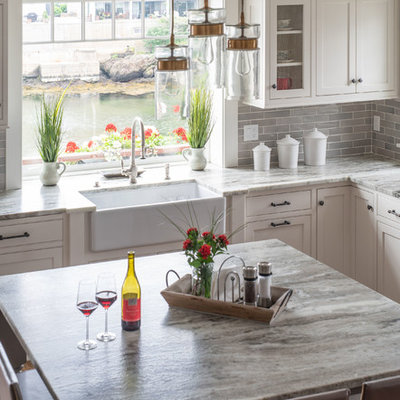 Inspiration for a large transitional l-shaped eat-in kitchen remodel in Boston with a farmhouse sink, beaded inset cabinets, white cabinets, marble countertops, gray backsplash, subway tile backsplash, stainless steel appliances, an island and gray countertops