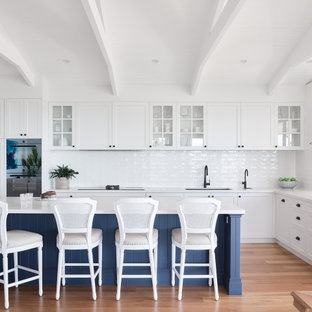 Design ideas for a large beach style l-shaped eat-in kitchen in Brisbane with an undermount sink, shaker cabinets, white cabinets, white splashback, panelled appliances, with island, beige floor and white benchtop.