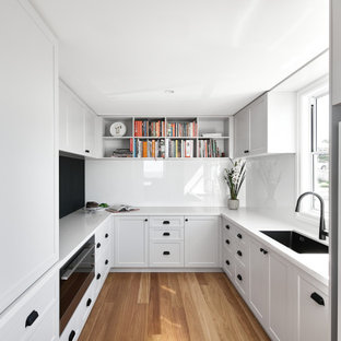 Photo of a mid-sized beach style u-shaped kitchen in Brisbane with an undermount sink, shaker cabinets, white cabinets, white splashback, black appliances, with island, brown floor and beige benchtop.