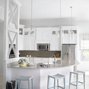 Foto på ett mellanstort vintage kök, med en rustik diskho, luckor med infälld panel, vita skåp, beige stänkskydd, stänkskydd i tunnelbanekakel, rostfria vitvaror, en köksö och bänkskiva i kvartsit