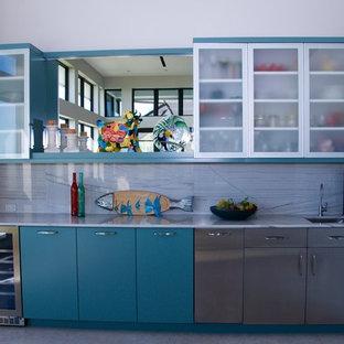 Foto di una grande cucina design con ante di vetro, ante turchesi, elettrodomestici in acciaio inossidabile e isola