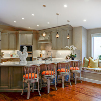 Inspiration for a tropical l-shaped medium tone wood floor and orange floor enclosed kitchen remodel in Miami with an undermount sink, beaded inset cabinets, distressed cabinets, gray backsplash, mosaic tile backsplash, paneled appliances and a peninsula