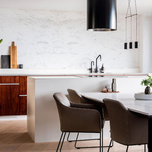 Design ideas for a small contemporary galley eat-in kitchen in Sydney with flat-panel cabinets, marble benchtops, white splashback, marble splashback, light hardwood floors, with island, white benchtop, dark wood cabinets and brown floor.