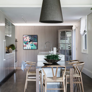 This is an example of a traditional galley eat-in kitchen in Sydney with an undermount sink, flat-panel cabinets, grey cabinets, black appliances, dark hardwood floors, with island and white benchtop.