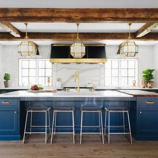 Exempel på ett klassiskt u-kök, med skåp i shakerstil, blå skåp, vitt stänkskydd, integrerade vitvaror, ljust trägolv och en köksö