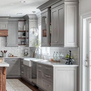 シアトルのトランジショナルスタイルのおしゃれなキッチン (エプロンフロントシンク、落し込みパネル扉のキャビネット、グレーのキャビネット、白いキッチンパネル、シルバーの調理設備、無垢フローリング、茶色い床、白いキッチンカウンター) の写真