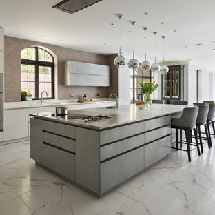 Design ideas for an expansive contemporary open plan kitchen in London with flat-panel cabinets, white cabinets, granite worktops, an island, white worktops and white floors.