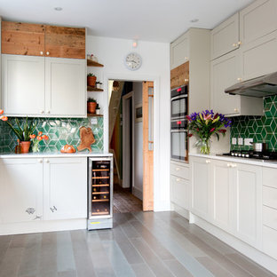 Inspiration for a medium sized classic single-wall open plan kitchen in London with green splashback, ceramic splashback, porcelain flooring, a submerged sink, shaker cabinets, beige cabinets and stainless steel appliances.