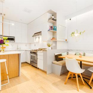 Modelo de cocina en L, moderna, pequeña, abierta, con fregadero bajoencimera, armarios con paneles lisos, puertas de armario blancas, encimera de cuarcita, salpicadero blanco, electrodomésticos de acero inoxidable, suelo de madera clara, una isla y suelo beige
