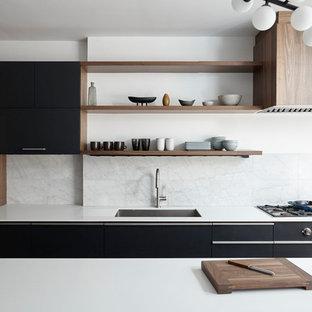 Diseño de cocina comedor lineal, minimalista, de tamaño medio, con fregadero bajoencimera, armarios con paneles lisos, puertas de armario negras, encimera de cuarcita, salpicadero blanco, salpicadero de travertino, electrodomésticos con paneles, suelo de madera clara, una isla y suelo beige
