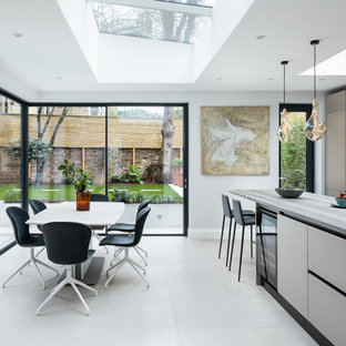 Photo of a contemporary kitchen/diner in London with a submerged sink, flat-panel cabinets, grey cabinets, an island, beige floors and white worktops.