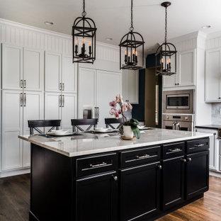 フィラデルフィアの広いトランジショナルスタイルのおしゃれなキッチン (フラットパネル扉のキャビネット、白いキャビネット、御影石カウンター、白いキッチンパネル、大理石のキッチンパネル、シルバーの調理設備、クッションフロア、茶色い床、黒いキッチンカウンター、エプロンフロントシンク) の写真