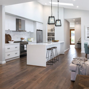 Transitional galley kitchen in Sydney with an undermount sink, shaker cabinets, white cabinets, white splashback, stainless steel appliances, dark hardwood floors, with island, brown floor, white benchtop and vaulted.