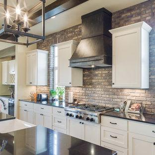 デンバーの中サイズのカントリー風おしゃれなキッチン (エプロンフロントシンク、落し込みパネル扉のキャビネット、白いキャビネット、珪岩カウンター、茶色いキッチンパネル、シルバーの調理設備の、無垢フローリング、サブウェイタイルのキッチンパネル) の写真