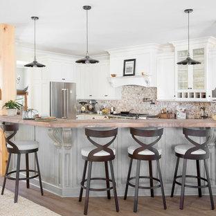 Ejemplo de cocina en U, de estilo de casa de campo, con armarios estilo shaker, puertas de armario blancas, salpicadero de ladrillos, electrodomésticos de acero inoxidable, suelo de madera oscura, una isla, suelo marrón y salpicadero rojo