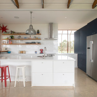 Inspiration for a contemporary l-shaped eat-in kitchen in Adelaide with an undermount sink, flat-panel cabinets, white cabinets, white splashback, stainless steel appliances, concrete floors, with island, beige floor and white benchtop.