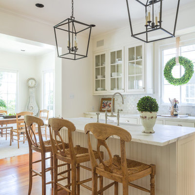 Mid-sized elegant l-shaped kitchen photo in New Orleans with glass-front cabinets, white cabinets, multicolored backsplash and an island