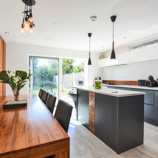 Inspiration for a contemporary kitchen/diner in Other with flat-panel cabinets, grey cabinets, brown splashback, wood splashback, an island, beige floors and white worktops.