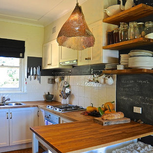 This is an example of a country u-shaped kitchen in Adelaide with a double-bowl sink, open cabinets, medium wood cabinets, wood benchtops, white splashback, stainless steel appliances and medium hardwood floors.