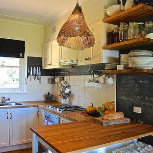 Réalisation d'une cuisine chalet en U avec un évier 2 bacs, un placard sans porte, des portes de placard en bois brun, un plan de travail en bois, une crédence blanche, un électroménager en acier inoxydable et un sol en bois brun.
