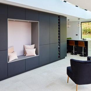 Ejemplo de cocina en L, contemporánea, de tamaño medio, con armarios con paneles lisos, puertas de armario negras, encimera de cuarcita, salpicadero rosa, una isla y encimeras grises