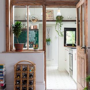ロンドンの小さいエクレクティックスタイルのおしゃれなキッチン (一体型シンク、シェーカースタイル扉のキャビネット、白いキャビネット、大理石カウンター、緑のキッチンパネル、セラミックタイルのキッチンパネル、パネルと同色の調理設備、セメントタイルの床、アイランドなし、白い床) の写真