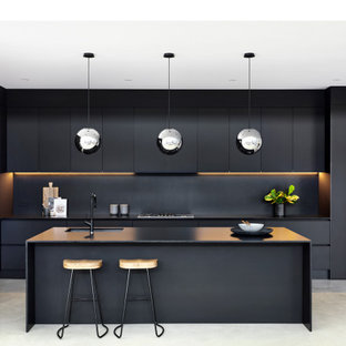 Photo of a large contemporary galley kitchen in Sydney with an undermount sink, flat-panel cabinets, black cabinets, concrete floors, grey floor, black benchtop, quartz benchtops, black splashback, stone slab splashback, stainless steel appliances and no island.