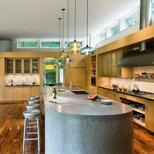 Immagine di una cucina a L design con lavello a doppia vasca, ante di vetro, ante in legno chiaro, top in cemento, paraspruzzi multicolore, paraspruzzi con piastrelle a mosaico, pavimento in legno massello medio e isola