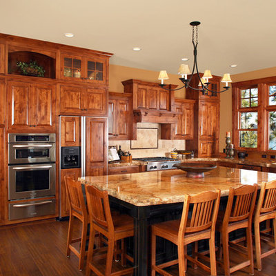 Inspiration for a rustic l-shaped kitchen remodel in Other with raised-panel cabinets, dark wood cabinets, granite countertops and paneled appliances
