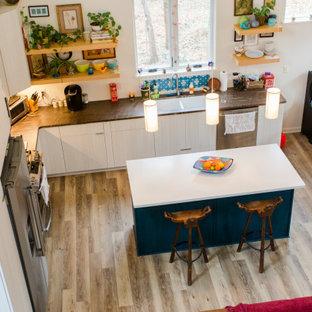 他の地域の中くらいのモダンスタイルのおしゃれなキッチン (ダブルシンク、フラットパネル扉のキャビネット、白いキャビネット、タイルカウンター、青いキッチンパネル、セラミックタイルのキッチンパネル、シルバーの調理設備、無垢フローリング、赤い床、茶色いキッチンカウンター) の写真