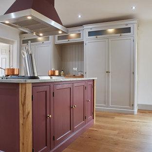 他の地域の大きいトラディショナルスタイルのおしゃれなキッチン (エプロンフロントシンク、シェーカースタイル扉のキャビネット、紫のキャビネット、御影石カウンター、カラー調理設備、無垢フローリング、茶色い床、白いキッチンカウンター) の写真
