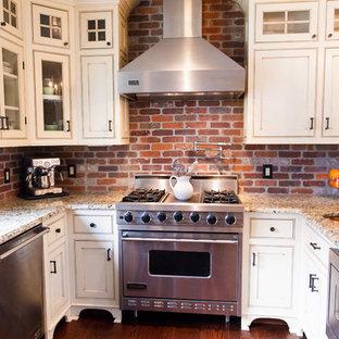 Geräumige Country Wohnküche ohne Insel in U-Form mit Landhausspüle, weißen Schränken, Granit-Arbeitsplatte, Küchenrückwand in Rot, Küchengeräten aus Edelstahl, braunem Holzboden, Schrankfronten im Shaker-Stil und Rückwand aus Backstein in New York