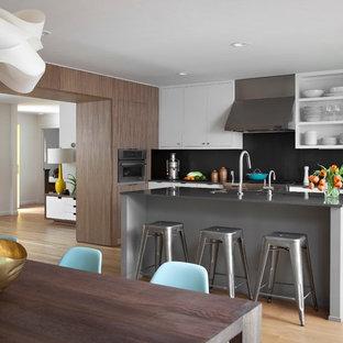 Ispirazione per una cucina moderna con lavello sottopiano, ante lisce, ante bianche, top in quarzo composito, paraspruzzi nero, paraspruzzi con piastrelle di metallo e elettrodomestici in acciaio inossidabile