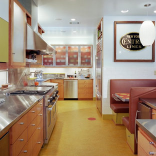 Design ideas for an eclectic kitchen in Austin with stainless steel appliances, stainless steel benchtops, flat-panel cabinets, medium wood cabinets, metallic splashback, metal splashback and yellow floor.